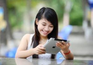 Woman using ipad looking at digital video ads.