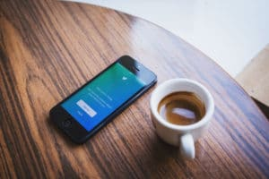 Cup of Coffee next to phone showing that digital recruitment is more important than ever.