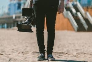 Cameraman holding a big camera, ready to shoot awesome digital video shorts.